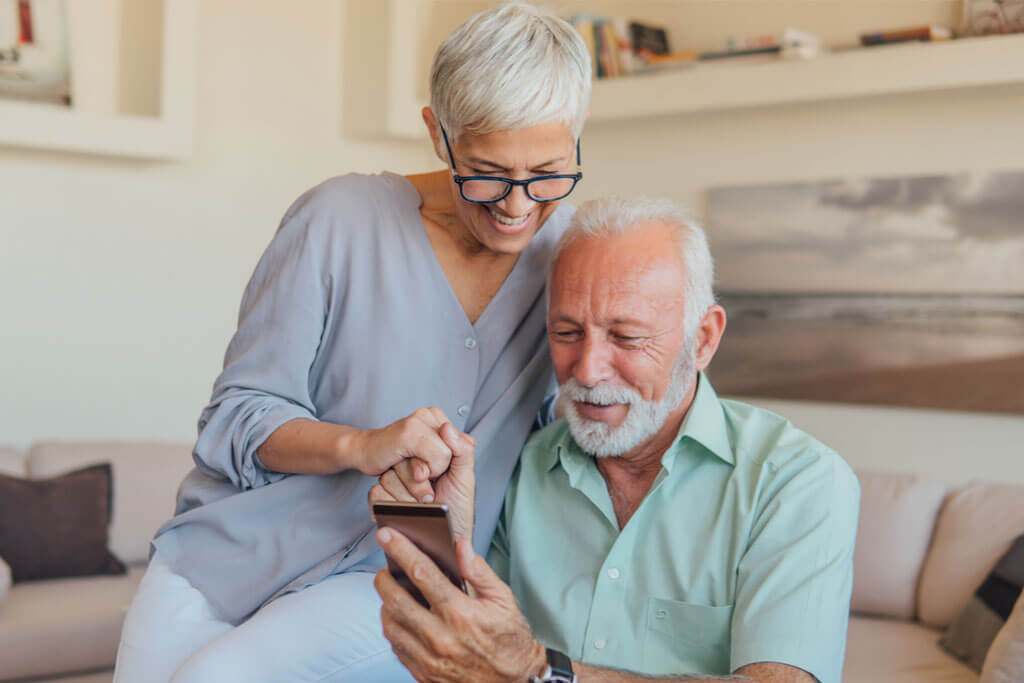 Online Hearing Canada older couple using smartphone app on bluetooth phone.